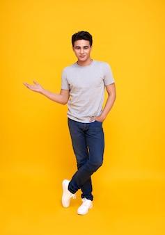 Przystojny młody mężczyzna azji, uśmiechając się i stojąc z gestem otwartej dłoni na żółto.