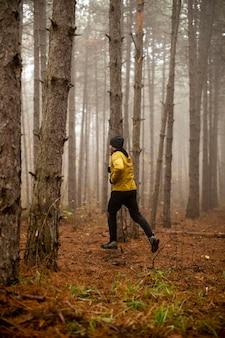 Przystojny młody mężczyzna biegający w jesiennym lesie i ćwiczący do wyścigu wytrzymałościowego w maratonie terenowym