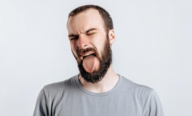 Przystojny młody mężczyzna brunetka marszczy brwi i zamyka oczy i wystaje język, zły na białej ścianie
