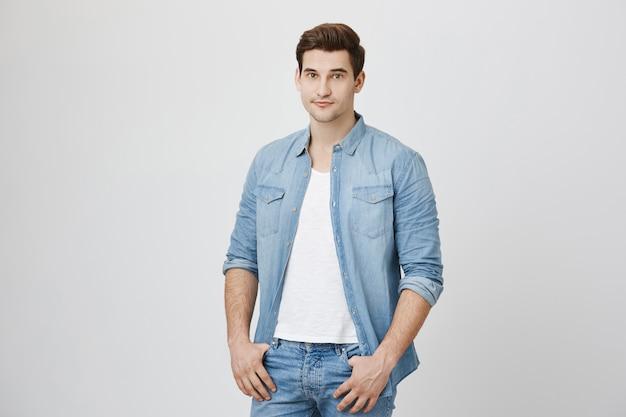 Przystojny młody mężczyzna brunetka uśmiecha się, trzymać ręce w kieszeniach
