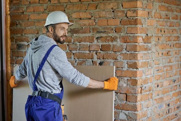 Przystojny młody mężczyzna budowniczy w kasku przy użyciu płyt kartonowo-gipsowych podczas pracy na budowie