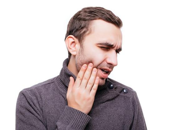Przystojny młody mężczyzna cierpiący na ból zęba, dotyka policzka, aby powstrzymać ból na białej ścianie