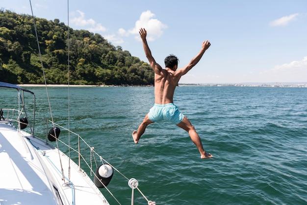 Przystojny młody mężczyzna cieszy czas na łodzi