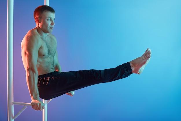 Przystojny młody mężczyzna ćwiczy na poziomym pasku przed ścianą neonową, robi ćwiczenia abs