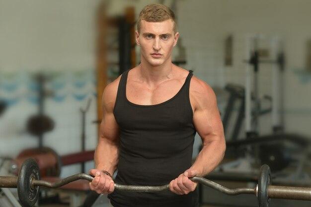 Przystojny młody mężczyzna ćwiczy na siłowni