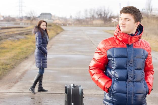 Przystojny młody mężczyzna czeka na drodze z walizką stojącą cierpliwie z rękami w kieszeniach, podczas gdy młoda kobieta przechodzi za nim