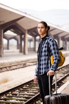 Przystojny młody mężczyzna czeka na pociąg