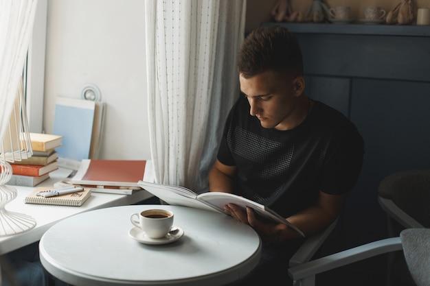 Przystojny młody mężczyzna czyta książkę. kawa na stole.