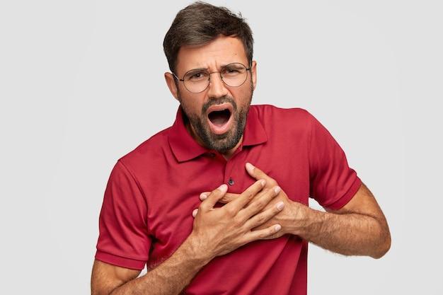 Przystojny młody mężczyzna emocjonalne pozowanie na białej ścianie