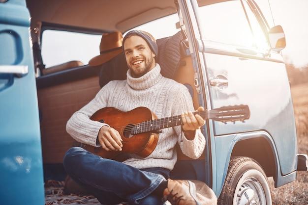 Przystojny młody mężczyzna gra na gitarze i uśmiecha się, spędzając czas w retro minivanie