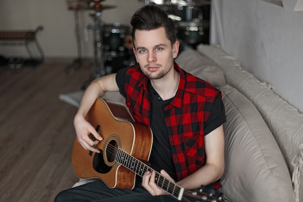 Przystojny młody mężczyzna gra na gitarze