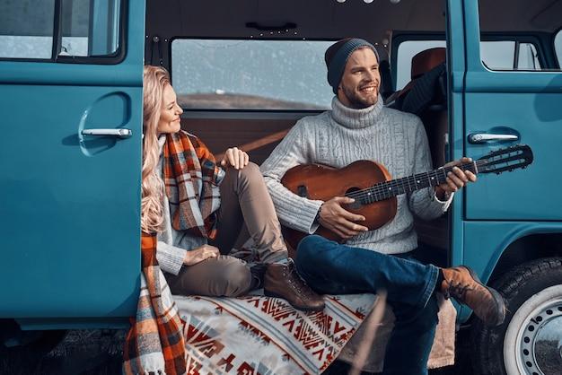 Przystojny młody mężczyzna grający na gitarze dla swojej dziewczyny podczas spędzania czasu w samochodzie kempingowym
