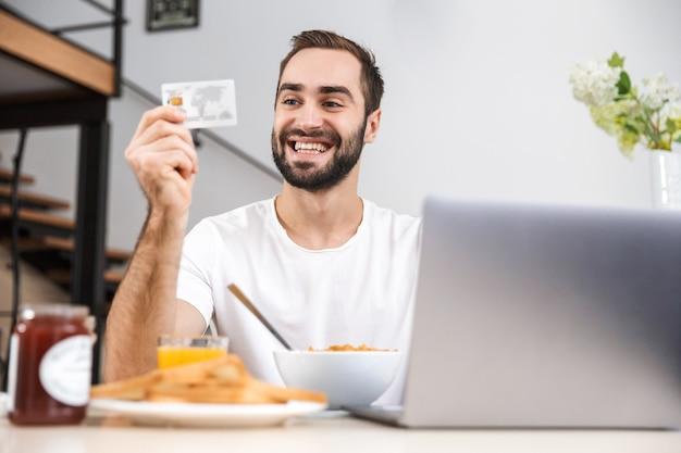 Przystojny młody mężczyzna jedząc śniadanie siedząc w kuchni, zakupy z laptopa i karty kredytowej