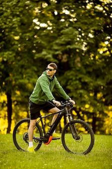 Przystojny młody mężczyzna jedzie ebike w parku