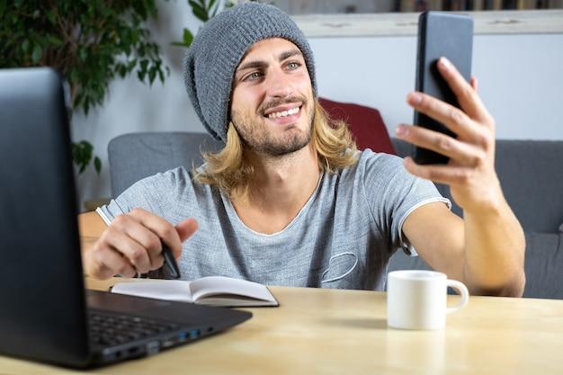 Przystojny młody mężczyzna kaukaski przy użyciu komputera pracującego w domu i telefon komórkowy czuje się szczęśliwy, uśmiechnięty