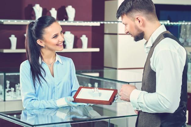 Przystojny młody mężczyzna kupuje biżuterię w lokalnym sklepie jubilerskim