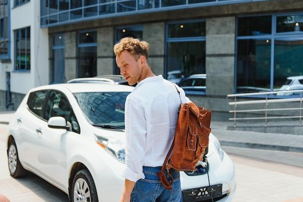 Przystojny młody mężczyzna ładuje swój nowoczesny samochód elektryczny.