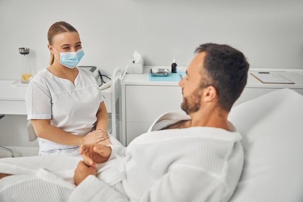 Przystojny młody mężczyzna leżący na kanapie i komunikujący się z żeńską kosmetyczką w masce medycznej