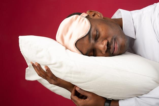 Przystojny młody mężczyzna leżący na poduszce