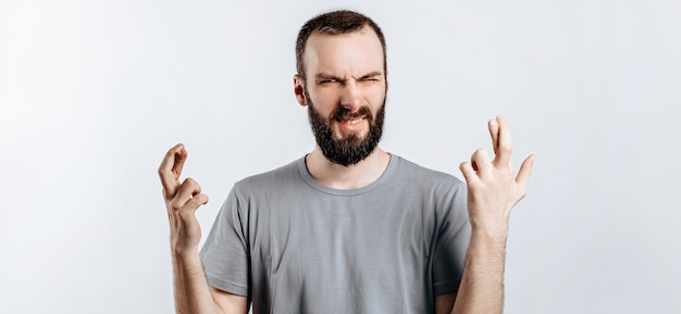 Przystojny młody mężczyzna marszczy brwi i krzyżuje palce w nadziei na białym tle z miejscem na makiety reklamowe