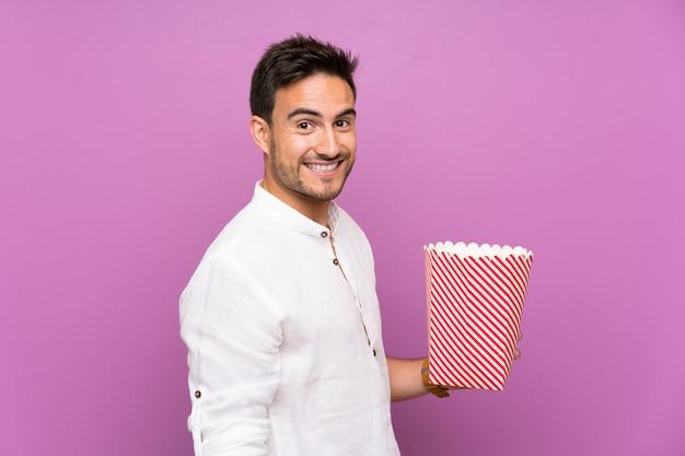 Przystojny młody mężczyzna na fioletowe ściany gospodarstwa popcorns
