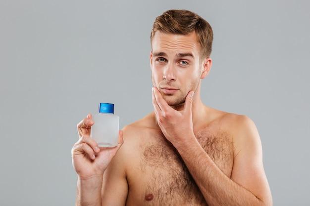 Przystojny młody mężczyzna nakłada balsam po goleniu na twarz na szarej ścianie