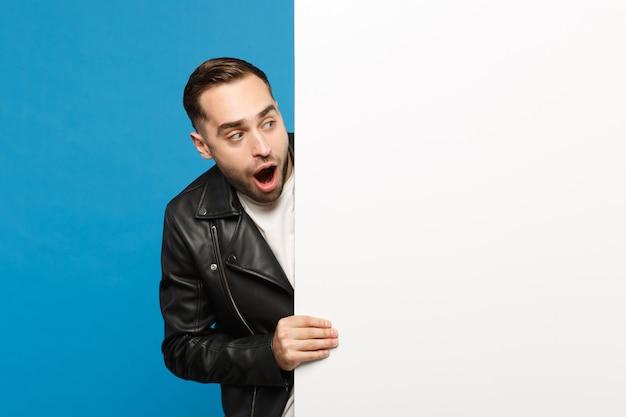 Przystojny młody mężczyzna nieogolony trzymać duży biały pusty pusty billboard dla treści promocyjnych na białym tle na tle niebieskiej ściany portret studio. koncepcja życia szczere emocje ludzi. makieta miejsca na kopię