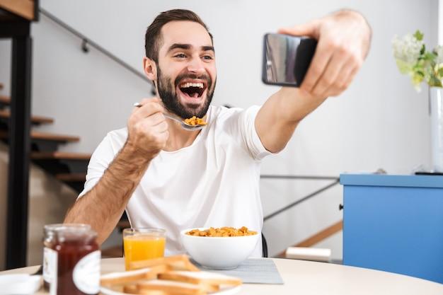 Przystojny młody mężczyzna o śniadanie siedząc w kuchni, biorąc selfie