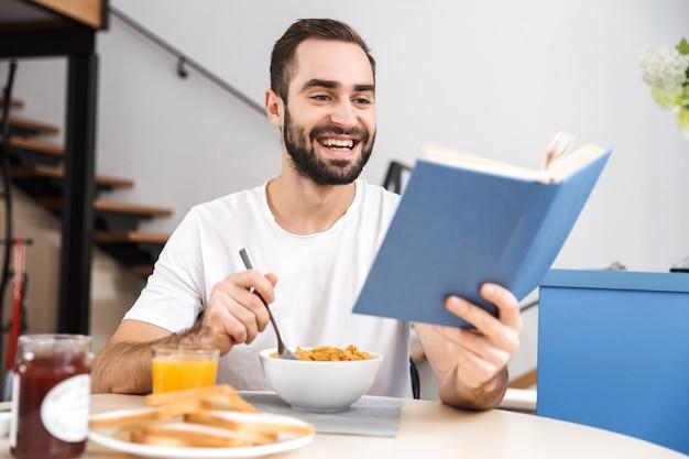Przystojny młody mężczyzna o śniadanie siedząc w kuchni, czytając książkę