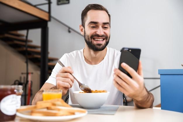 Przystojny młody mężczyzna o śniadanie siedząc w kuchni, trzymając telefon komórkowy