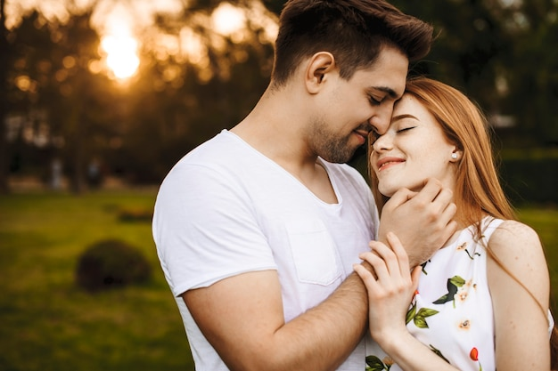 Przystojny młody mężczyzna obejmując przyjaciółkę, uśmiechając się i dotykając jej twarzy podczas randki przed zachodem słońca na zewnątrz w czasie wakacji.