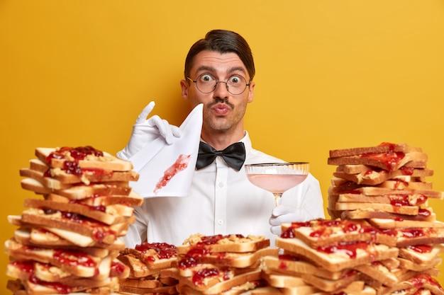 Przystojny młody mężczyzna otoczony galaretowatą kanapkami z masłem orzechowym