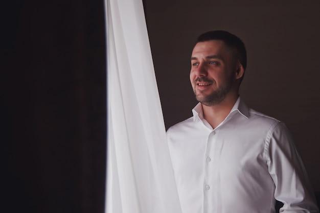 Przystojny młody mężczyzna pan młody ubiera białą koszulę w oknie w pokoju hotelowym, uśmiech z pewnością wygląda sam. słodki facet przygotowuje się na spotkanie z panną młodą. pojęcie szczęścia i luksusu żonaty. skopiuj miejsce