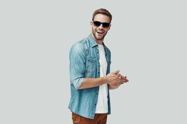 Przystojny młody mężczyzna patrzący na kamerę i uśmiechający się stojąc na szarym tle