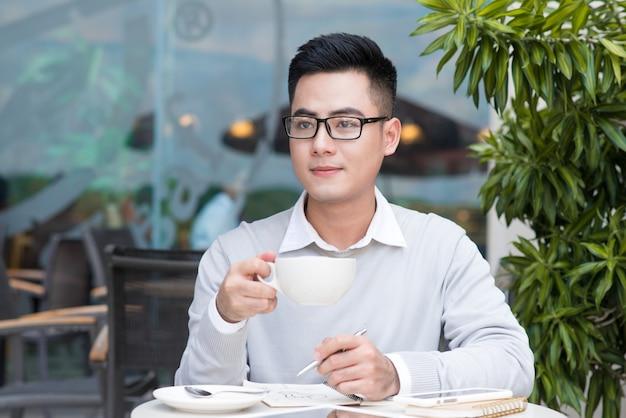 Przystojny młody mężczyzna pije kawę w mieście