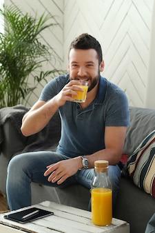 Przystojny młody mężczyzna pije sok pomarańczowy w domu