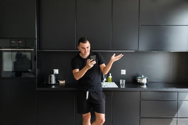 Przystojny młody mężczyzna pije wodę, rozmawia przez telefon komórkowy i uśmiecha się stojąc w kuchni w domu
