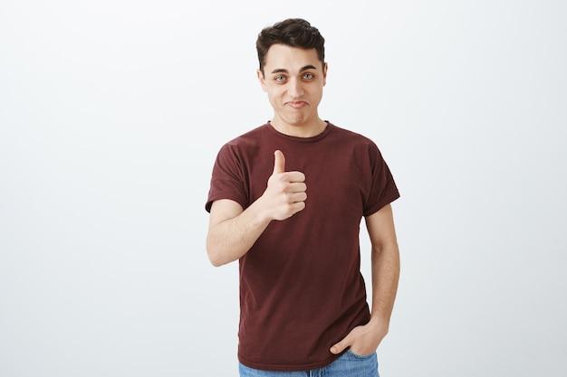 Przystojny młody mężczyzna pokazuje kciuk do góry. dobra robota!