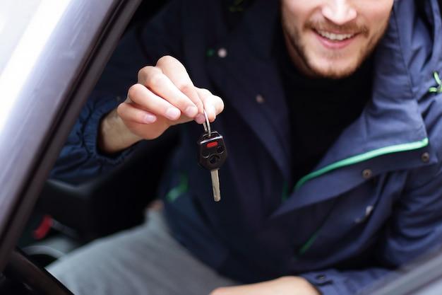Przystojny młody mężczyzna pokazuje kluczyk do nowego samochodu