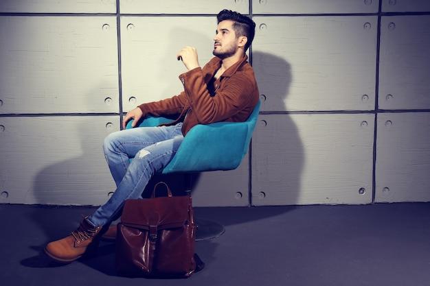 Przystojny młody mężczyzna pozowanie. kurtka, buty, dżinsy, okulary przeciwsłoneczne.