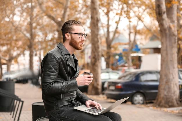 Przystojny młody mężczyzna pracuje na laptopie na zewnątrz