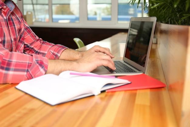 Przystojny młody mężczyzna pracuje na laptopie przy stole