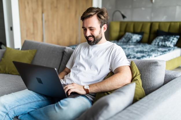 Przystojny młody mężczyzna pracuje na swoim laptopie, relaksując się na kanapie w domu