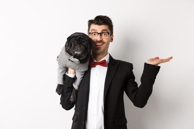 Przystojny młody mężczyzna przedstawiający produkt dla zwierząt domowych pod ręką, trzymający uroczego czarnego psa na ramieniu i uśmiechający się, pokazując coś na białym tle