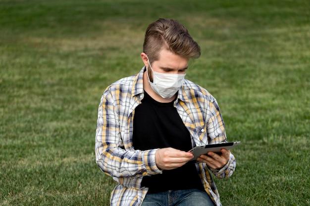 Przystojny młody mężczyzna przeglądania maski na twarz