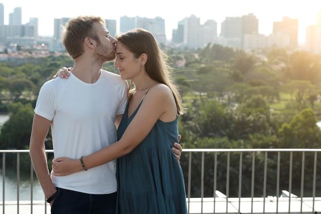 Przystojny młody mężczyzna przytula dziewczynę i całuje ją w czoło, gdy stoją na budynku...