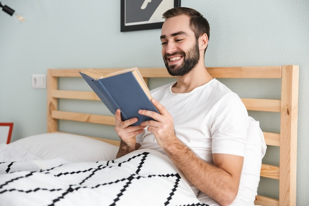 Przystojny młody mężczyzna r. w łóżku, pracując na komputerze przenośnym, czytając książkę