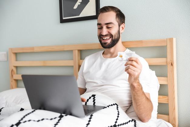 Przystojny młody mężczyzna r. w łóżku, pracując na komputerze przenośnym, pokazując plastikową kartę kredytową