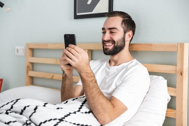 Przystojny młody mężczyzna r. w łóżku, trzymając telefon komórkowy