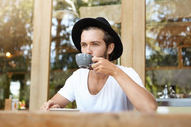 Przystojny młody mężczyzna rasy kaukaskiej w kapeluszu trzyma filiżankę kawy